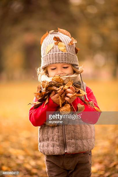 Cute little boy with bunch of leaves in his hands.