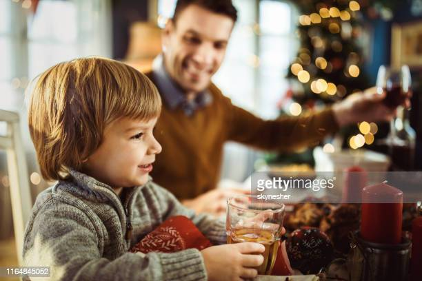 cute little boy with glass of juice at dining table. - new year's day stock pictures, royalty-free photos & images