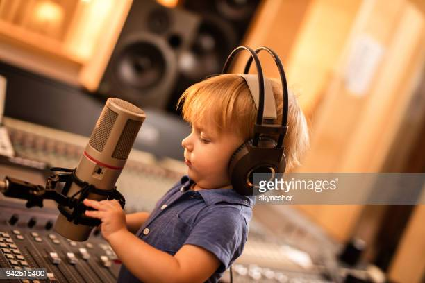 Cute little boy with headphones talking on a microphone in a radio station.