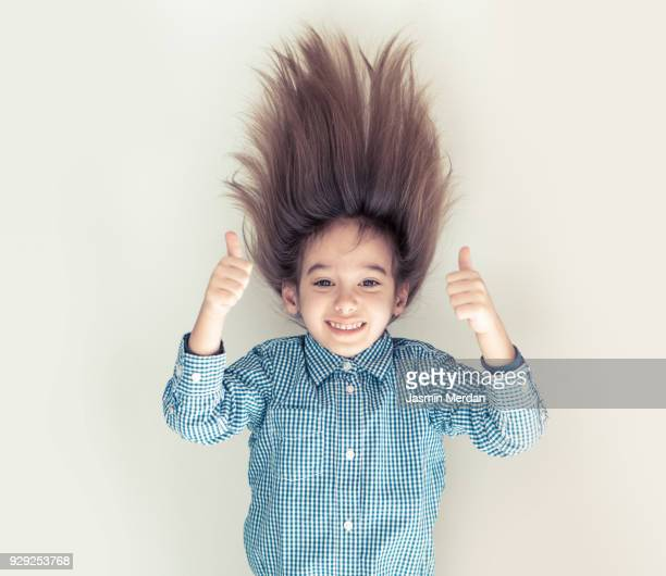 Cute little boy with long hair upside down