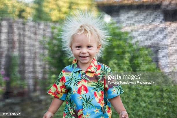 cute little boy with static electricy hair, having his funny portrait taken outdoors on a trampoline - strom haare stock-fotos und bilder
