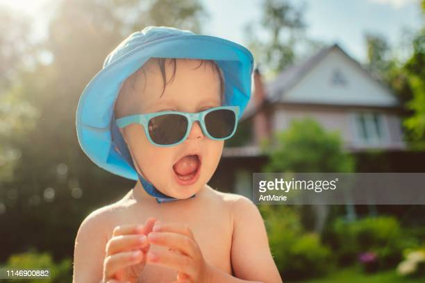 cute little boy with sunglasses at back yard in summer - sun hat stock pictures, royalty-free photos & images