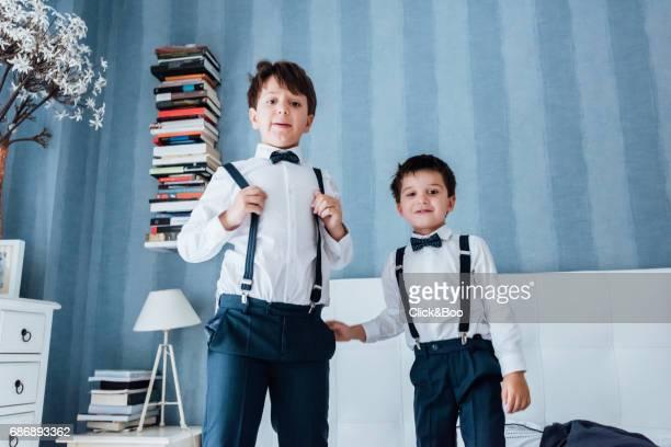 cute little boys playing indoors - サスペンダー ストックフォトと画像