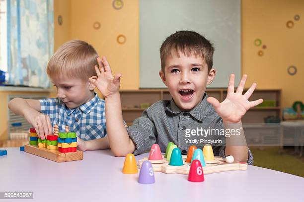 Cute little boys playing with toys at table in classroom