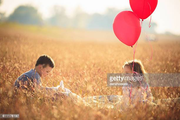 Cute little brother and sister playing with balloons outdoor
