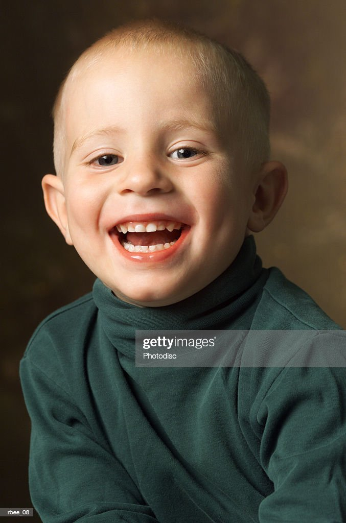 cute little caucasian boy wearing green turtleneck smiles open mouthed with expression of happiness : Stockfoto