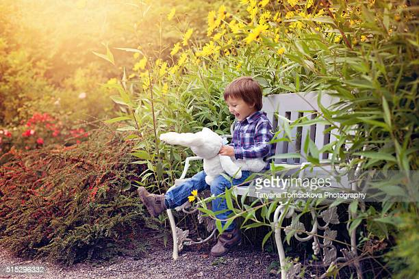 Cute little caucasian child, boy, holding fluffy toy, hugging it, in the park, on sunny spring day