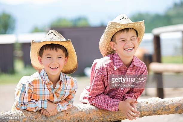 Cute little cowboys in hats leaning against fence post