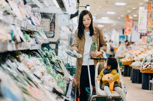 Cute little daughter sitting in a shopping cart grocery shopping for fresh organic vegetables with young Asian mother in a supermarket - gettyimageskorea