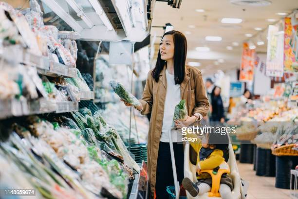 cute little daughter sitting in a shopping cart grocery shopping for fresh organic vegetables with young asian mother in a supermarket - homemaker stock pictures, royalty-free photos & images