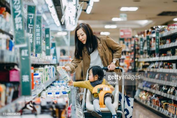 cute little daughter sitting in a shopping cart grocery shopping for dairy product with young asian mother in a supermarket - consumerism stock pictures, royalty-free photos & images