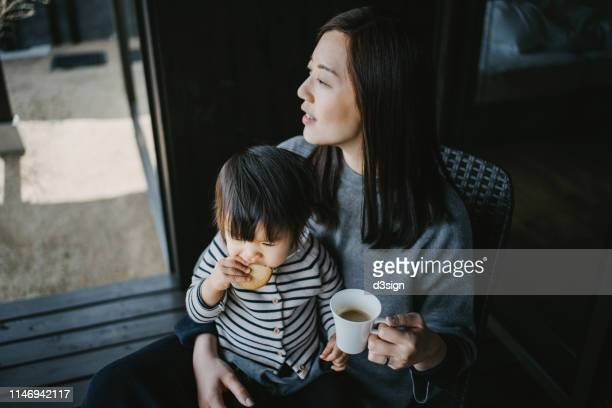 cute little daughter sitting on mother's lap eating cookie while mother drinking coffee, they are relaxing on the balcony and enjoying intimate family time together - シンプルな暮らし ストックフォトと画像