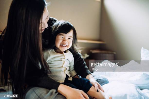 cute little daughter smiling joyfully and sitting on mother's lap after waking up in the morning - two generation family stock pictures, royalty-free photos & images