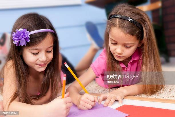 cute little elementary-age girls enjoy working on school project. - beautiful mexican girls stock photos and pictures