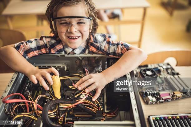 schattige kleine ingenieur repareren van kapotte computer in de klas. - computeronderdeel stockfoto's en -beelden