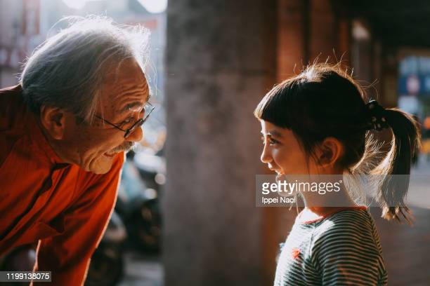 cute little eurasian girl smiling at japanese grandfather with sunlight - back lit stock pictures, royalty-free photos & images
