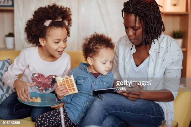 Cute little family looking at tablet and eating breakfast