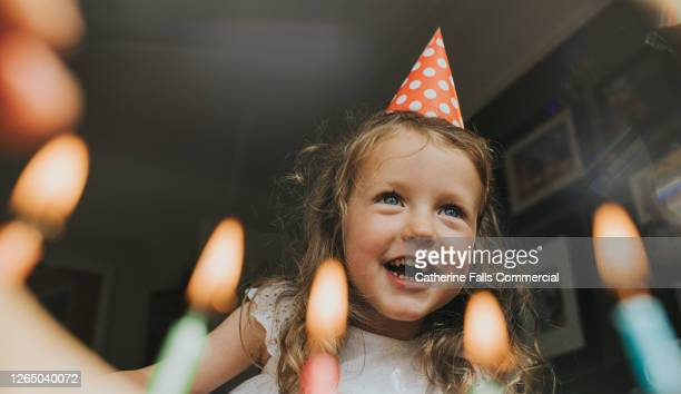 cute little girl above a birthday cake, about to blow out the candles. - love emotion stock pictures, royalty-free photos & images