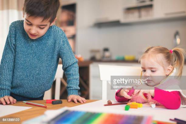 Cute little girl and boy playing with plasteline