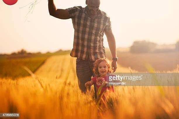 Cute little girl and father with balloons at field