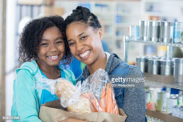 cute little girl and her mom donate groceries to food bank - food pantry stock pictures, royalty-free photos & images