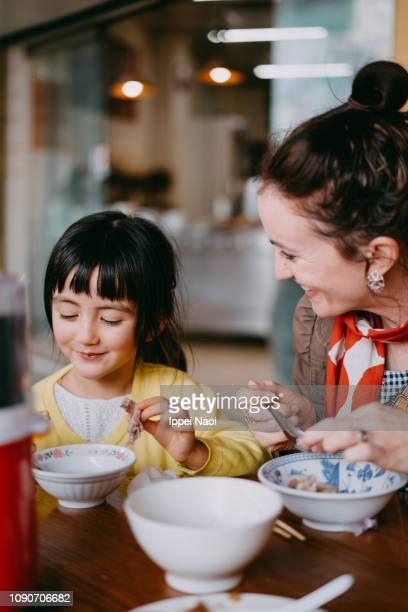 Cute little girl and mother enjoying Chinese street food