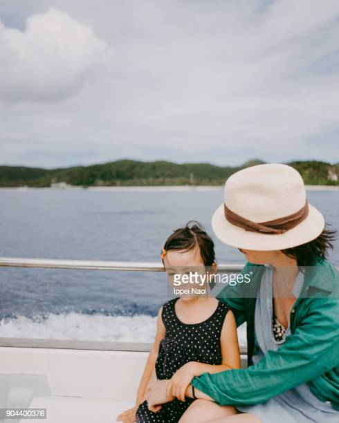 Cute little girl and mother having intimate moment on boat
