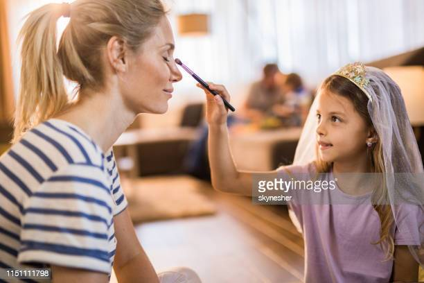 cute little girl applying make-up on her mother's eyes at home. - incidental people stock pictures, royalty-free photos & images