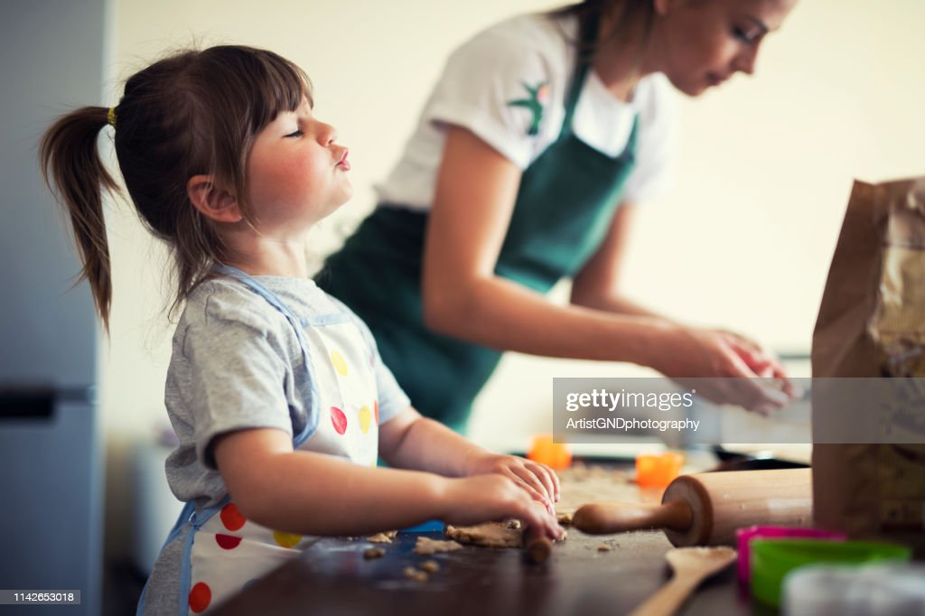 Cute little girl baking at home with mom : Stock Photo