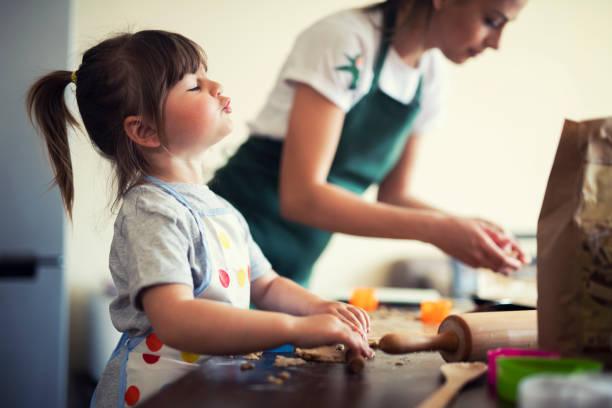 可愛的小女孩烤在家裡與媽媽 - 焗 預備食物 個照片及圖片檔
