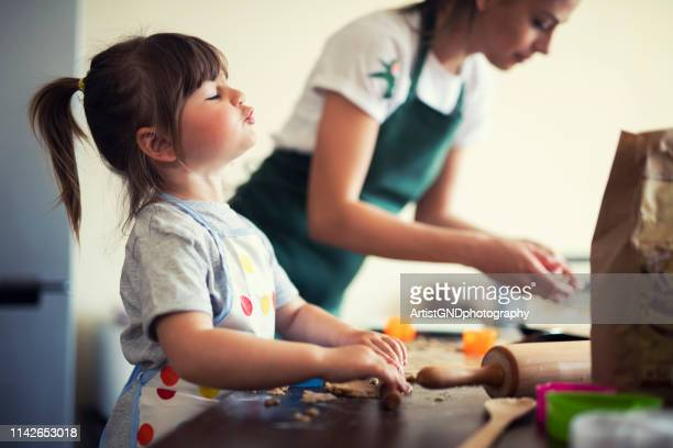 cute little girl baking at home with mom - offspring stock pictures, royalty-free photos & images