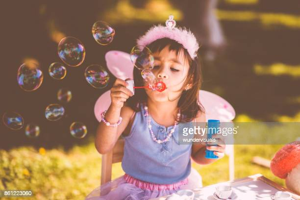 cute little girl blowing bubbles at garden spring tea party - fairy stock photos and pictures