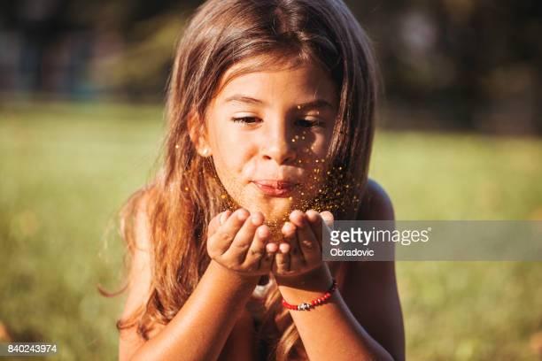 Niedliche kleine Mädchen bläst Goldglitter in einem park