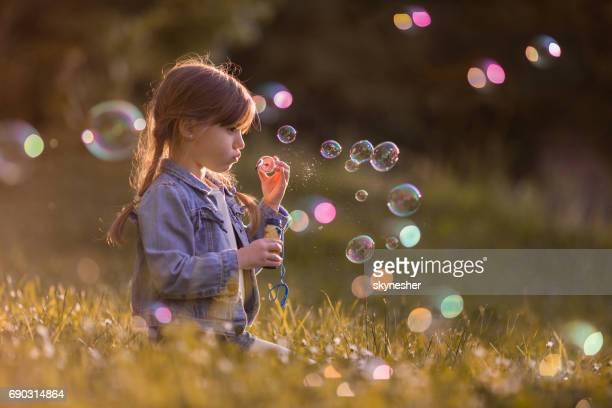 Schattig klein meisje blazen van zeepbellen in het park.
