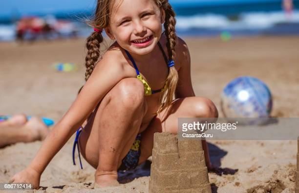 Niedliche kleine Mädchen Gebäude Sandburg am Sandstrand