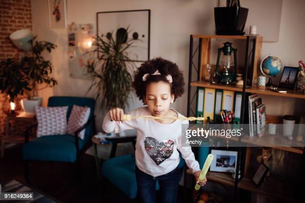 Cute little girl climbing on armchair