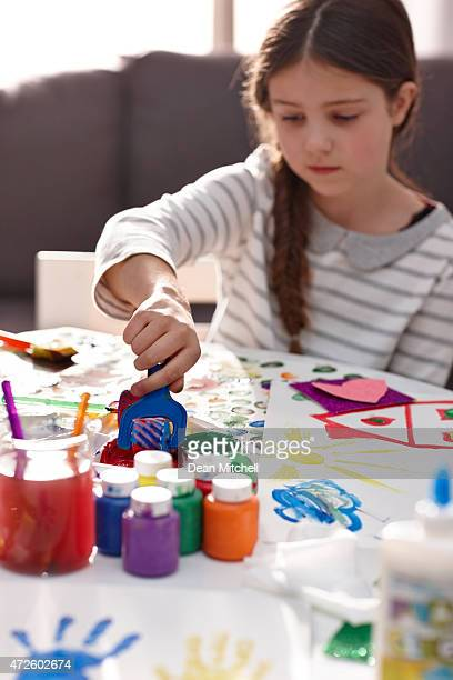 Cute little girl creating artwork from colours