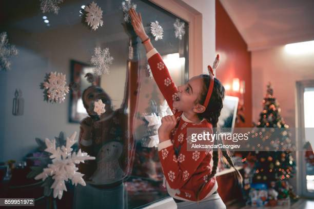 Cute Little Girl Decorate her Room with Christmas Ornaments