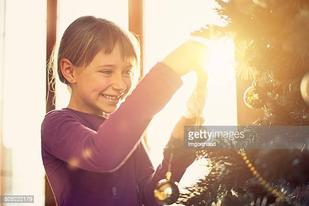 Cute little girl decorating christmas tree