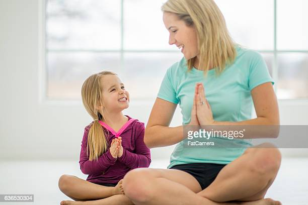 Cute Little Girl Doing Yoga with Her Mom