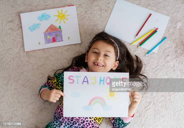 cute little girl drawing pictures at home with a stay at home saying on the paper - stay at home order stock pictures, royalty-free photos & images
