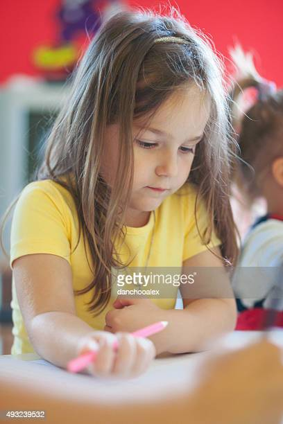 Cute little girl drawing with crayons