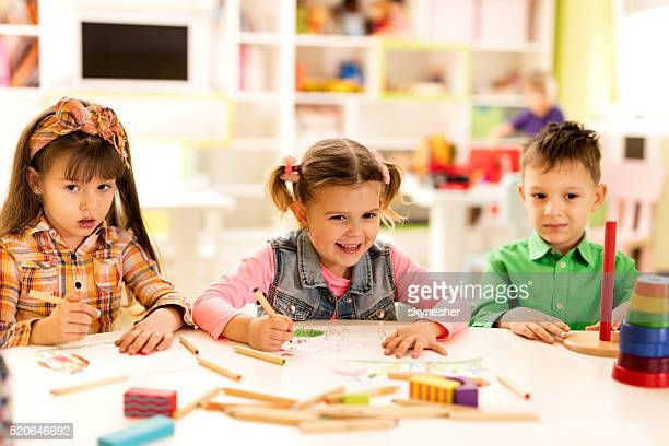 Cute little girl drawing with friends in kindergarten.