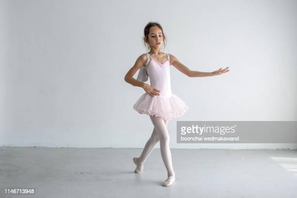 cute little girl dreams of becoming a ballerina. child girl in a pink tutu dancing in a room. - balletttänzer stock-fotos und bilder