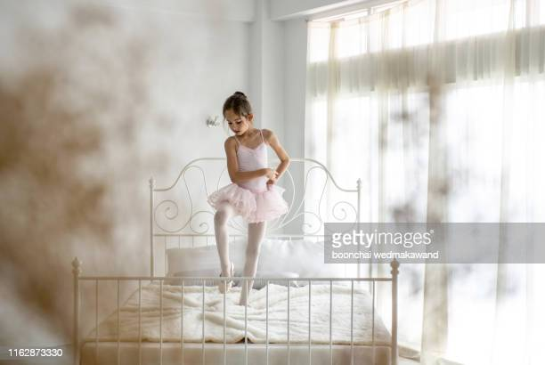 cute little girl dreams of becoming a ballerina. child girl in a pink tutu dancing in a room. - pink skirt stock pictures, royalty-free photos & images