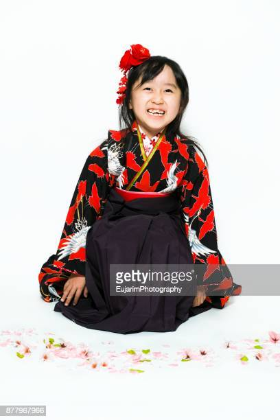 Cute little girl dressed in kimono sitting on the floor covered with cherry blossom petals