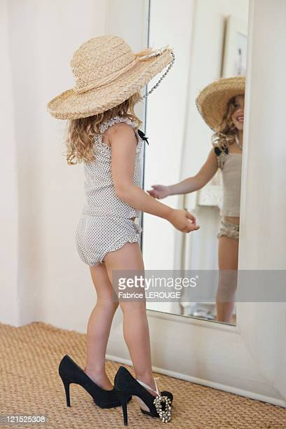 Cute little girl dressed like her mother in oversized accessories and looking at mirror