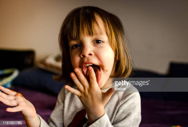 かわいい女の子はチョコレートを食べる - 口を使う ストックフォトと画像
