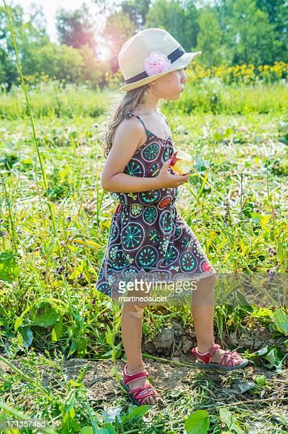 Niedliche kleine Mädchen isst einen Apfel in einem Feld.