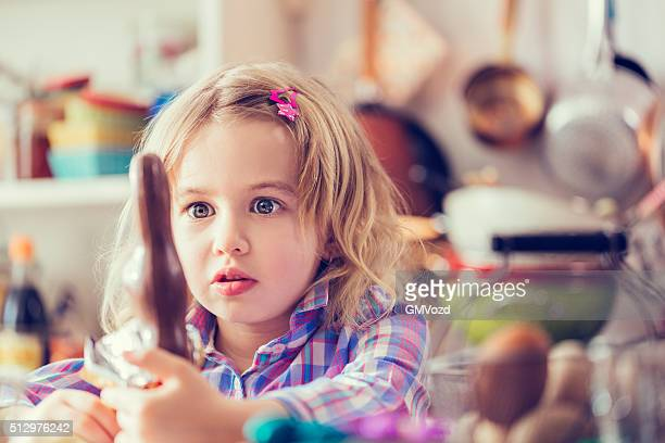 Cute Little Girl Eating Chocolate Easter Bunny